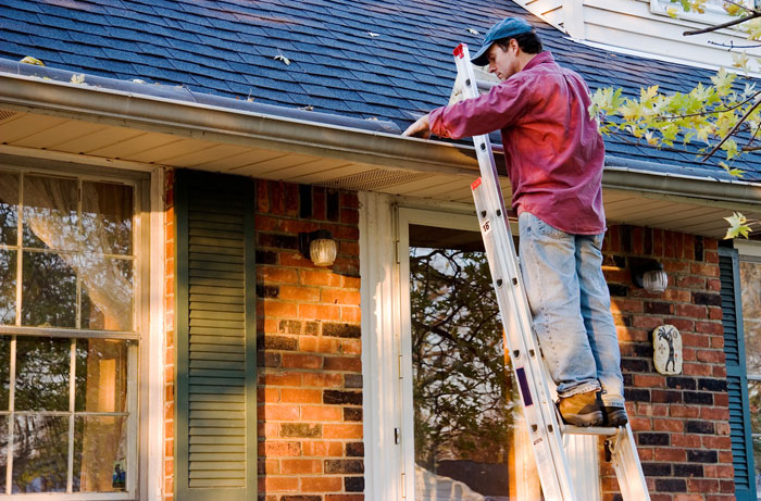 homeowner on ladder cleaning gutters and roof in grand rapids michigan